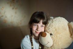 Niña que abraza el oso de peluche interior en su sitio, concepto de la dedicación, juguete de Big Bear fotografía de archivo
