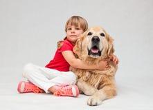 Niña que abraza el perro grande del golden retriever Imagenes de archivo