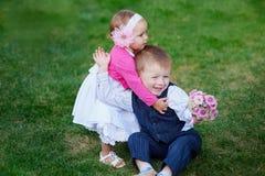Niña que abraza a un muchacho con un ramo de flores en parque fotografía de archivo