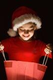 Niña que abre un regalo mágico de la Navidad Foto de archivo libre de regalías