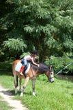 Niña que acaricia un caballo mientras que montar a caballo de lomo de caballo imágenes de archivo libres de regalías