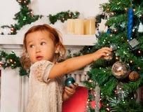 Niña que adorna el árbol de navidad Fotos de archivo