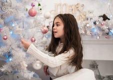 Niña que adorna el árbol de navidad Imagen de archivo libre de regalías