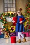 Niña que adorna el árbol de navidad Navidad Año Nuevo Muchos ornamentos y regalos del día de fiesta holiday indoor Hogar foto de archivo