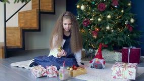 Niña que adorna el árbol de navidad con los juguetes metrajes