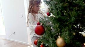 Niña que adorna el árbol de navidad en casa almacen de metraje de vídeo