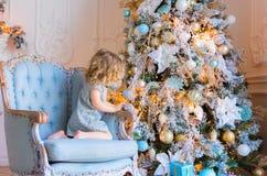 Niña que adorna el árbol de navidad que se sienta en la butaca Fotos de archivo