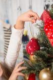 Niña que adorna el árbol del Año Nuevo en casa Fotos de archivo libres de regalías