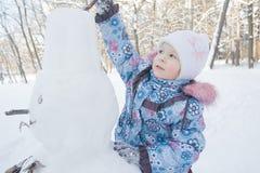 Niña que adorna el muñeco de nieve del invierno Foto de archivo