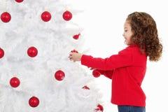Niña que adorna un árbol de navidad Imagen de archivo