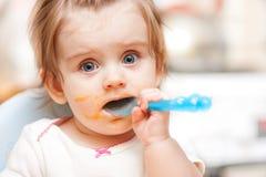 Niña que alimenta desde una cuchara en silla azul Fotografía de archivo libre de regalías