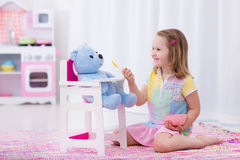 Niña que alimenta su oso del juguete Foto de archivo libre de regalías