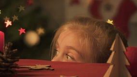 Niña que aparece de debajo la tabla, mirando alrededor, haciendo bromas de la Navidad almacen de metraje de vídeo