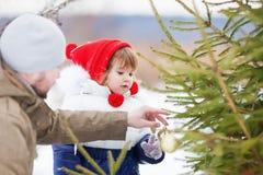 Niña que ayuda a su Navidad de adornamiento tres del padre al aire libre Fotos de archivo libres de regalías