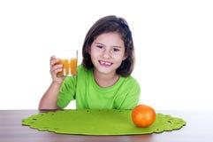 Niña que bebe el zumo de naranja Fotografía de archivo