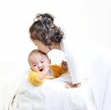 Niña que besa al bebé foto de archivo