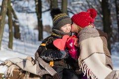 Niña que besa al muchacho con el regalo al aire libre Imagenes de archivo