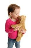 Niña que besa el oso de peluche Fotos de archivo
