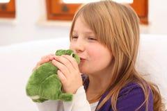 Niña que besa la rana del juguete en el sofá Foto de archivo