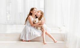 Niña que besa a su más vieja hermana mientras que se sienta en el piso Fotos de archivo libres de regalías