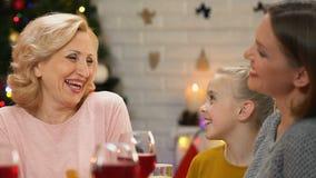 Niña que bromea con adultos en la tabla del día de fiesta, celebración de la feliz Navidad metrajes