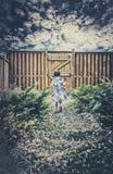 Niña que camina abajo de una trayectoria que sostiene una cesta de Pascua Foto de archivo