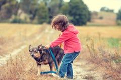 Niña que camina con el perro en el campo fotografía de archivo libre de regalías