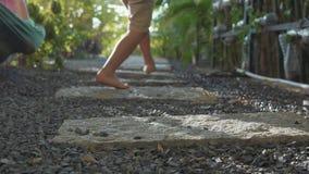 Niña que camina en la trayectoria en jardín Los pies del primer van lejos de cámara metrajes