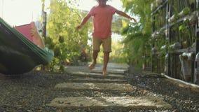 Niña que camina en la trayectoria en jardín Los pies del primer vienen cerca a la cámara almacen de metraje de vídeo