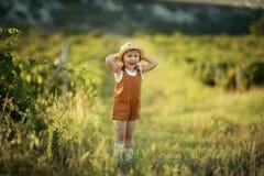 Ni?a que camina en un campo que lleva un sombrero de vaquero imagen de archivo