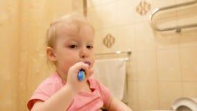 Niña que cepilla sus dientes con un cepillo de dientes en cuarto de baño por la mañana almacen de metraje de vídeo