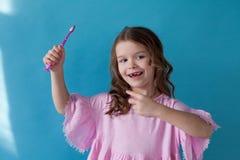 Niña que cepilla sus dientes con un diente de la odontología del cepillo de dientes imagenes de archivo