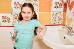 Niña que cepilla sus dientes en el cuarto de baño imagenes de archivo