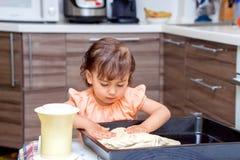Niña que cocina la comida en la cocina Fotos de archivo libres de regalías