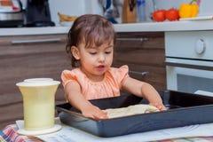 Niña que cocina la comida en la cocina Imagen de archivo libre de regalías