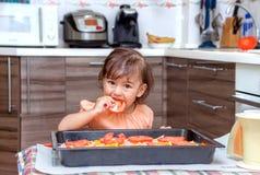 Niña que cocina la comida en la cocina Fotografía de archivo libre de regalías