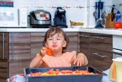 Niña que cocina la comida en la cocina Imagenes de archivo