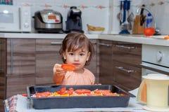 Niña que cocina la comida en la cocina Foto de archivo