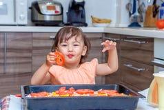 Niña que cocina la comida en la cocina Imagen de archivo