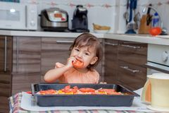 Niña que cocina la comida en la cocina Fotos de archivo