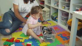 Niña que coge los juguetes en envase de plástico almacen de metraje de vídeo