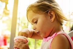 Niña que come el helado afuera imagenes de archivo