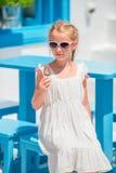 Niña que come el helado al aire libre en el verano en café al aire libre Imagen de archivo libre de regalías