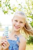 Niña que come el helado azul blanco sabroso Foto de archivo