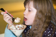 Niña que come el helado en café foto de archivo