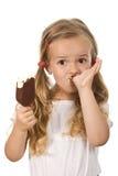 Niña que come el helado que lame los dedos Foto de archivo