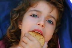Niña que come el retrato del primer de la galleta Fotografía de archivo
