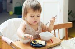 Niña que come en la sentada del bebé, pequeño niño que come friuts Foto de archivo
