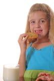 Niña que come la galleta de viruta de chocolate Imagen de archivo libre de regalías