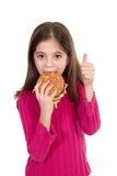 Niña que come la hamburguesa Imágenes de archivo libres de regalías